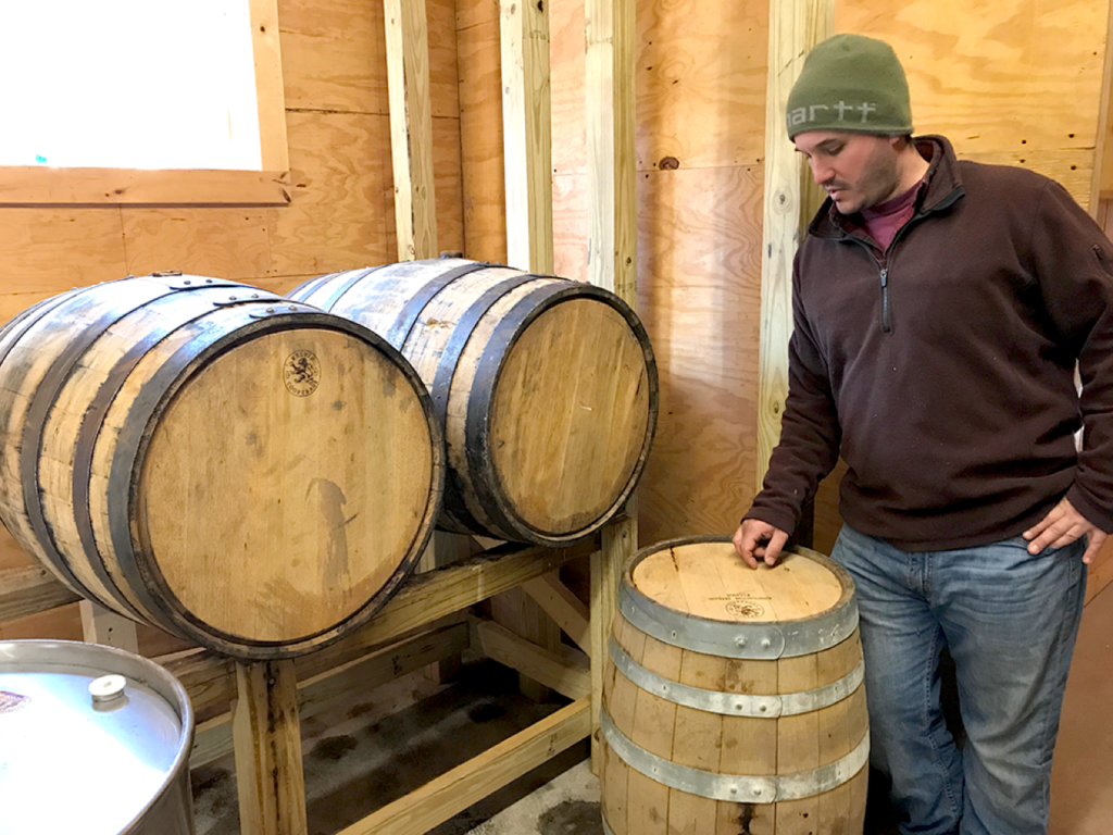 John Garigliano Next to Bourbon Barrels for Aging Syrup